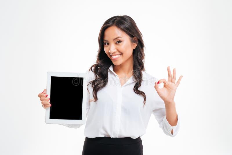 Asiatische Geschäftsfrau, die Tablette mit leerem Bildschirm hält und o.k. darstellt stockbild