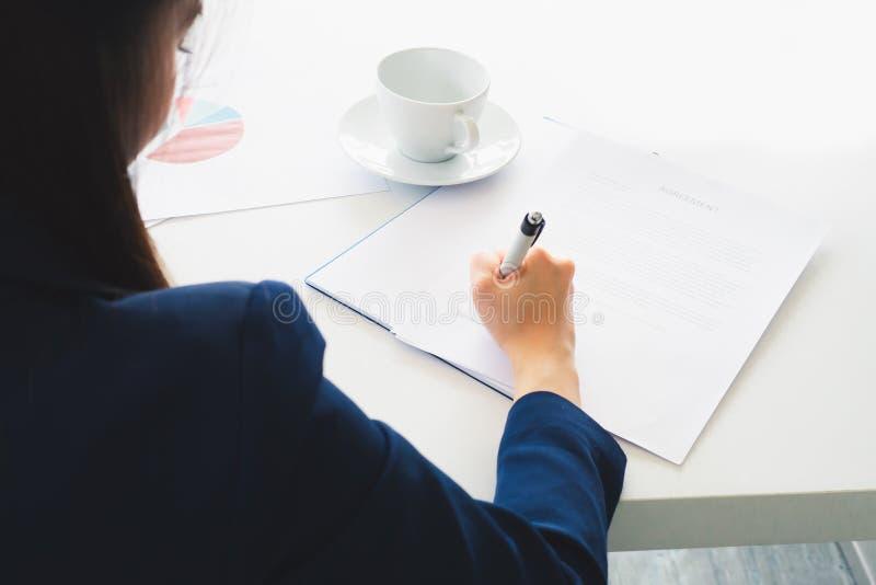 Asiatische Geschäftsfrau, die Unterzeichnung in Dokument schreibt lizenzfreie stockbilder