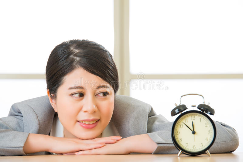 Asiatische Geschäftsfrau, die Wecker auf Schreibtisch betrachtet stockbilder