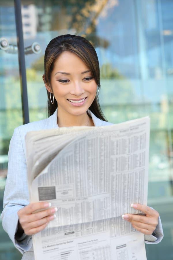 Asiatische Geschäftsfrau-Lesezeitung stockbild
