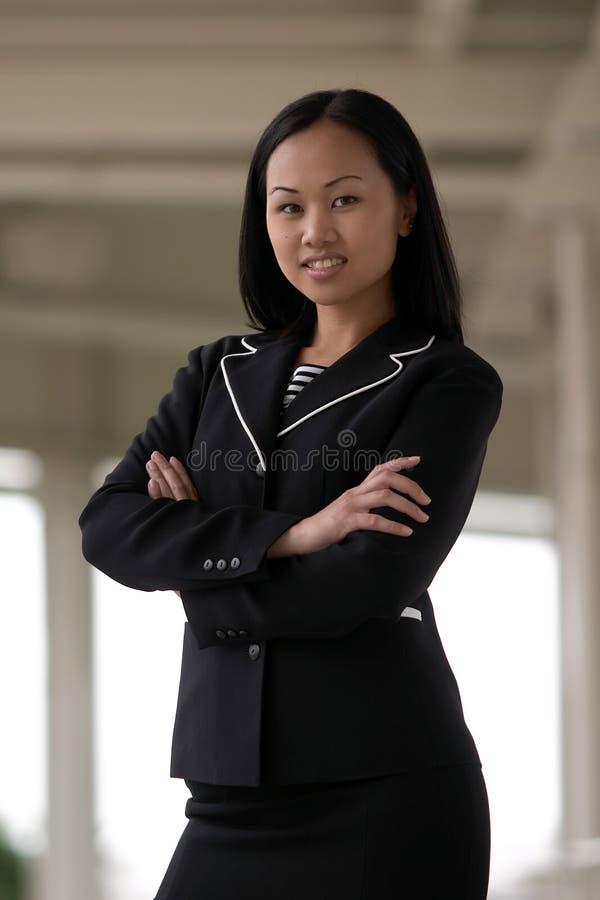 Asiatische Geschäftsfrau mit dem Arme gefalteten Lächeln lizenzfreies stockbild