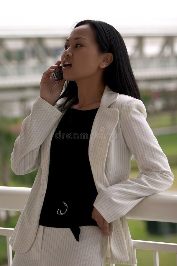 Asiatische Geschäftsfrau mit dem Handy, der weg schaut lizenzfreie stockfotos