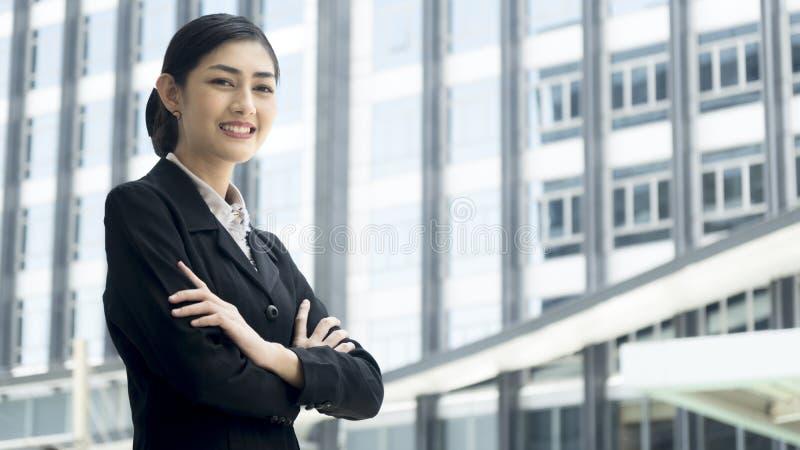 Asiatische Geschäftsfrau steht mit überzeugter Aufgabe an PU im Freien stockfoto