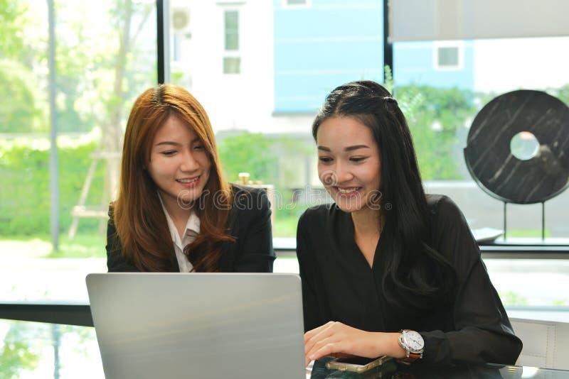 Asiatische Geschäftsfrauen, die Laptop im Konferenzzimmer bearbeiten und verwenden stockfotografie