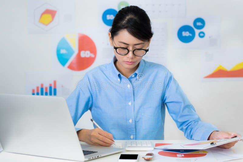 Asiatische Geschäftsfraulohnaufmerksamkeit beim Arbeits Geschäft und FI lizenzfreies stockfoto