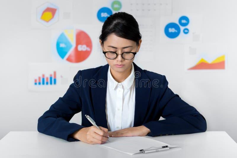 Asiatische Geschäftsfraulohnaufmerksamkeit beim Arbeits Geschäft und FI stockfoto
