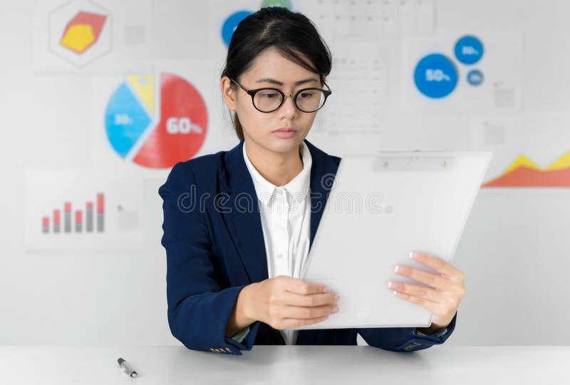 Asiatische Geschäftsfraulohnaufmerksamkeit beim Arbeits Geschäft und FI lizenzfreies stockbild