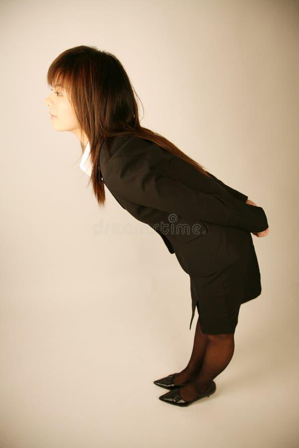 Asiatische Geschäftsfrauverbeugung stockbild