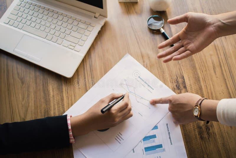 Asiatische Geschäftsleute, die über Bericht sprechen und mit Papierblatt arbeiten stockbilder