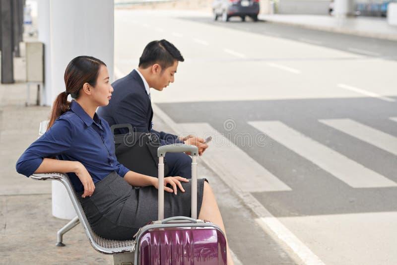 Asiatische Geschäftsleute, die auf Taxi im Flughafen warten stockfotos