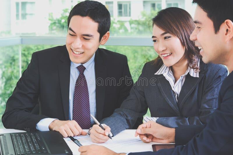 Asiatische Geschäftsleute, die in einer Sitzung sich besprechen und lächeln stockfotos