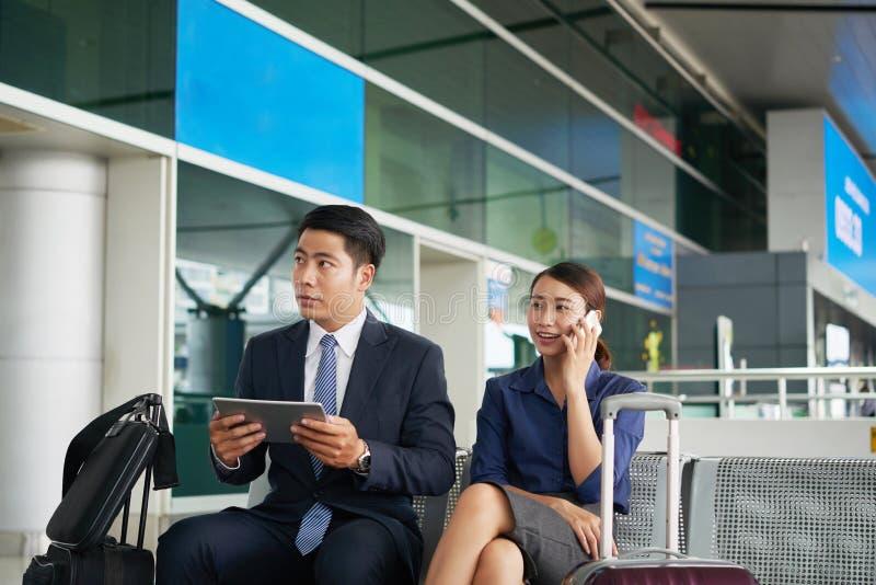 Asiatische Geschäftsleute, die in Flughafen warten lizenzfreie stockbilder