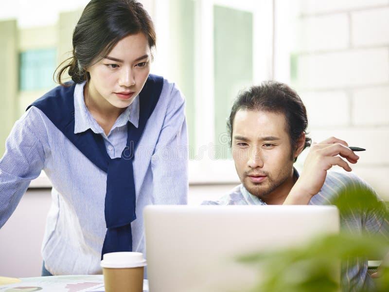 Asiatische Geschäftsleute, die im Büro zusammenarbeiten stockfotos