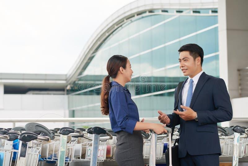 Asiatische Geschäftsleute, die im Flughafen sprechen lizenzfreie stockfotografie