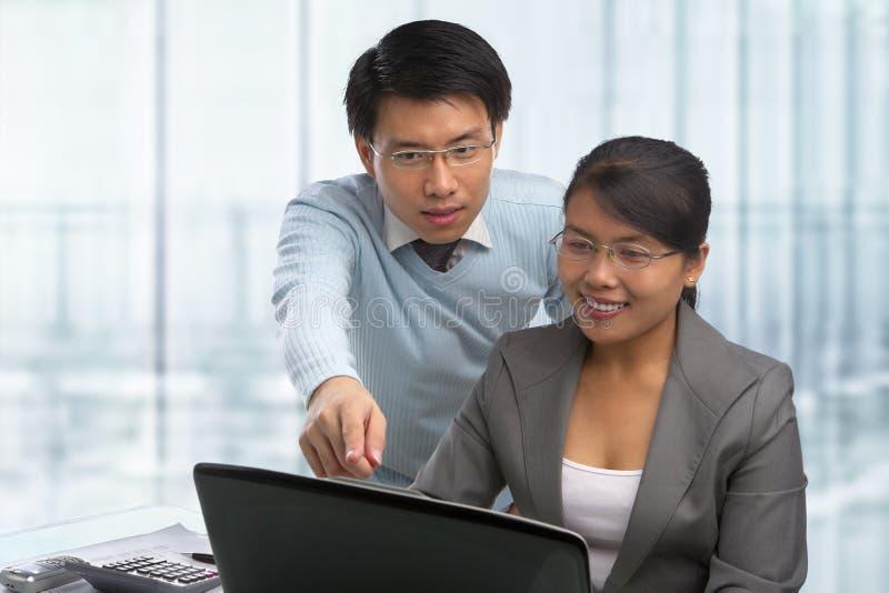 Asiatische Geschäftsleute, die zusammenarbeiten lizenzfreies stockfoto