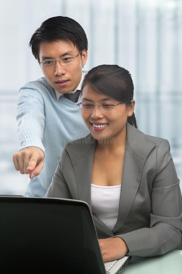 Asiatische Geschäftsleute, die zusammenarbeiten lizenzfreie stockbilder