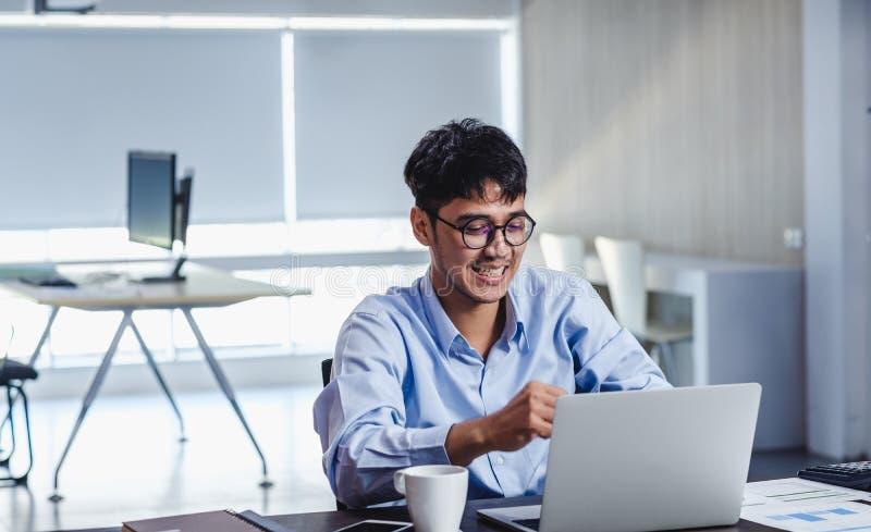 Asiatische Geschäftsleute feiern Erfolg, wenn sie in modernen Büros über Laptop auf dem Schreibtisch informiert werden stockbild