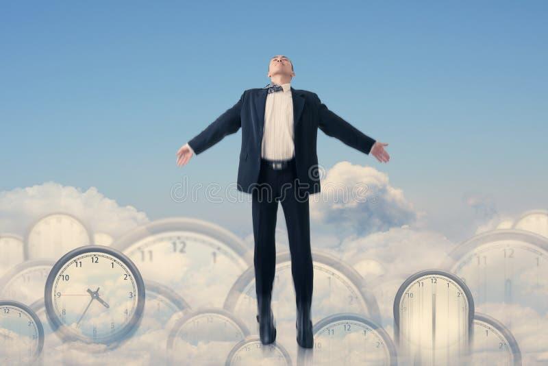 Asiatische Geschäftsmannfliege über Uhren stockbild