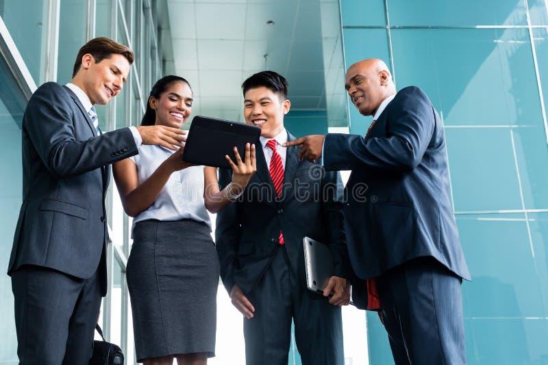 Asiatische Geschäftsteamdarstellung auf Tablette lizenzfreie stockbilder