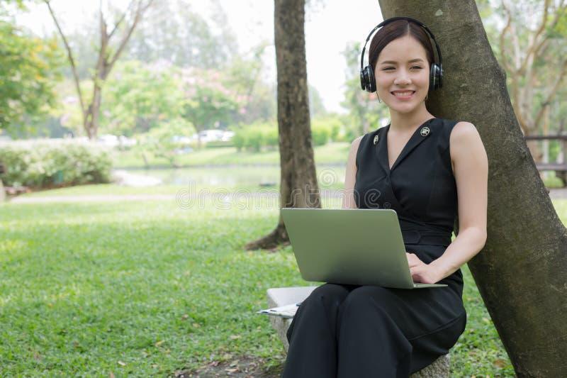 Asiatische Gesch?ftsfrau, vorbei sich zu entspannen sitzen im Garten mit Laptop und in h?render Musik vom Stereokopfh?rer lizenzfreie stockfotos