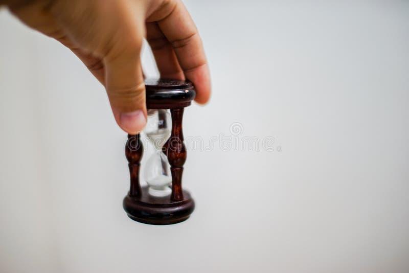Asiatische Hand, die eine Sanduhr auf weißem Hintergrund hält stockbilder