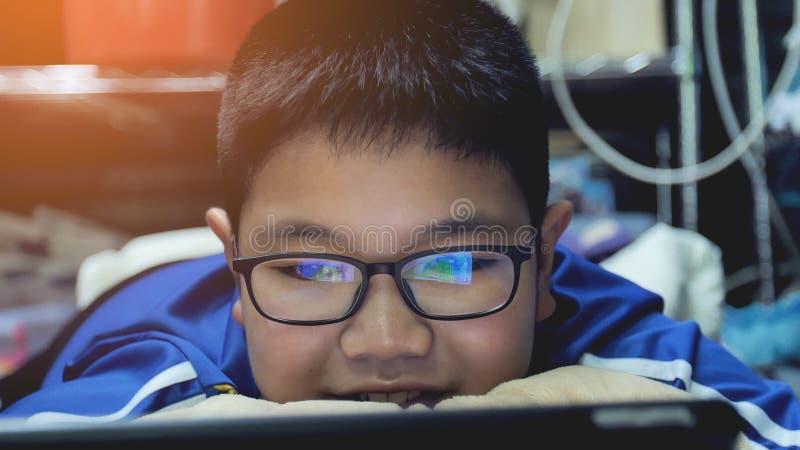 Asiatische Jugendliche, die auf Tablet-Computer, Lächelngesicht aufpassen lizenzfreie stockbilder