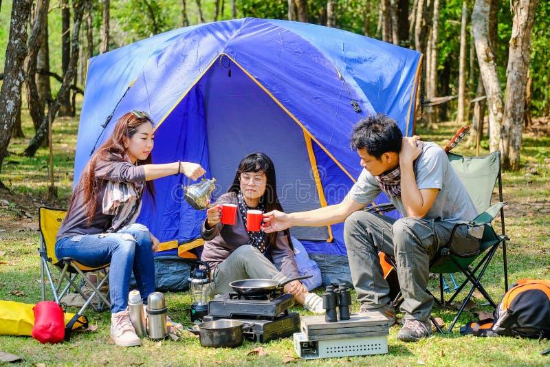 Asiatische Jugendlicher Kaffeemaschine mit roter Glasfront des blauen Segeltuchcampingzelts auf glücklichem Gesicht des Rasenfläc stockbild