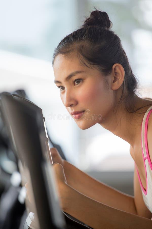 asiatische junge Eignungsfrau in der Sportkleidung trainierend mit dem Radfahren in Sportturnhallenclub Mädchentraining auf Fahrr lizenzfreie stockfotos