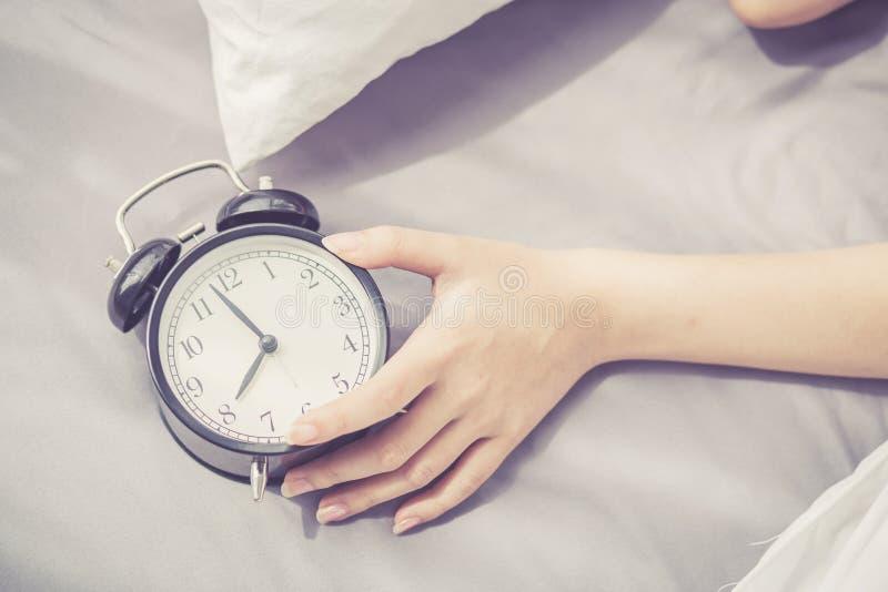 Asiatische junge Frau der Nahaufnahme stellen Wecker am guten Morgen, aufwachen für Schlaf mit dem Mädchen ab, das Wecker hält stockfotos