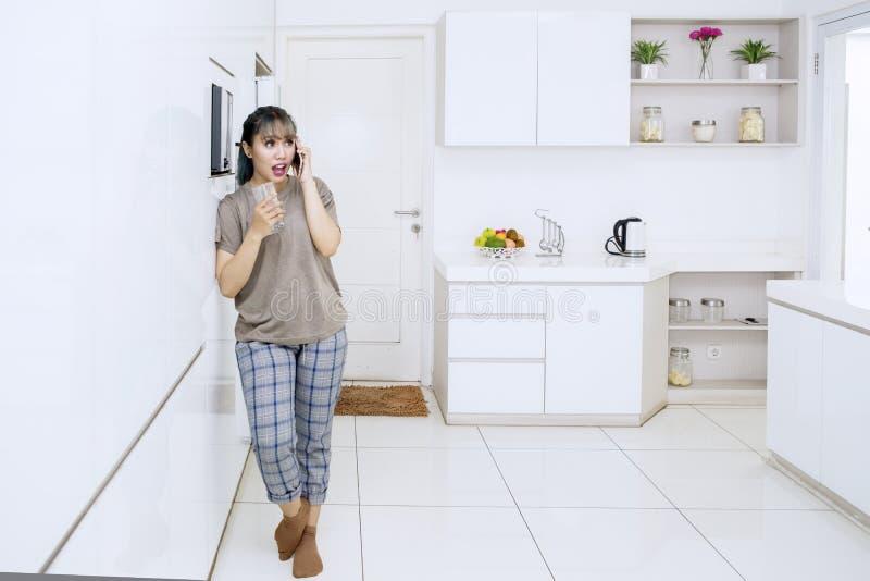 Asiatische junge Frau, die an einem Handy spricht stockfotos