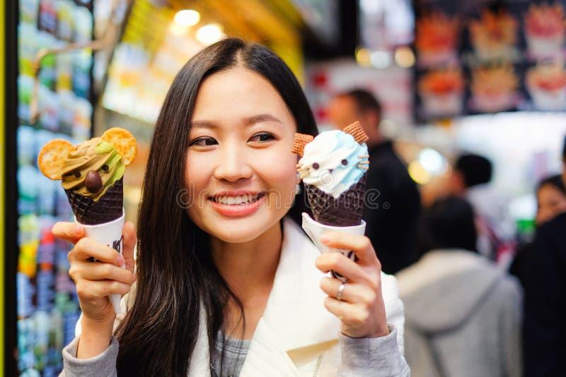 Asiatische junge Frau, die Straßenlebensmittel in Hong Kong isst stockbild