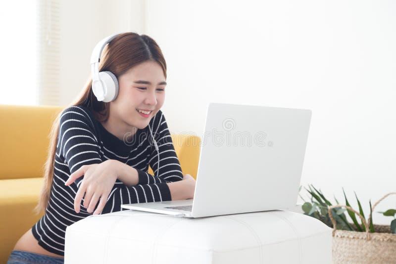 Asiatische junge Frau zufrieden gewesen mit dem Lernen von Sprache von on-line-Kursen mit Laptop, stockbilder