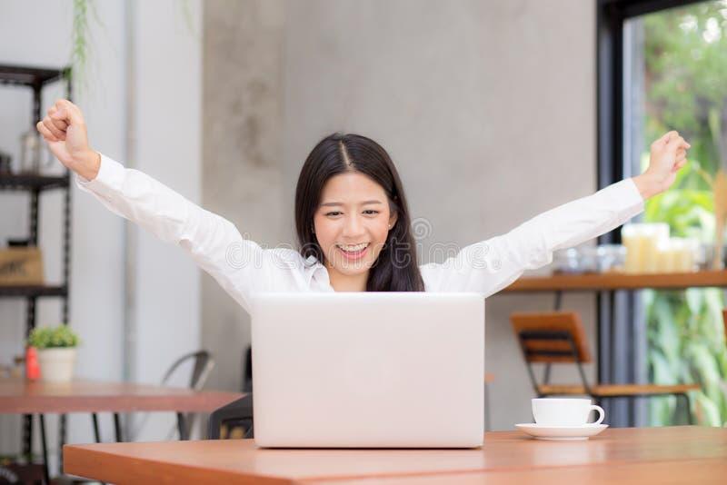 Asiatische junge Geschäftsfrau aufgeregt und froh vom Erfolg mit Laptop stockbild