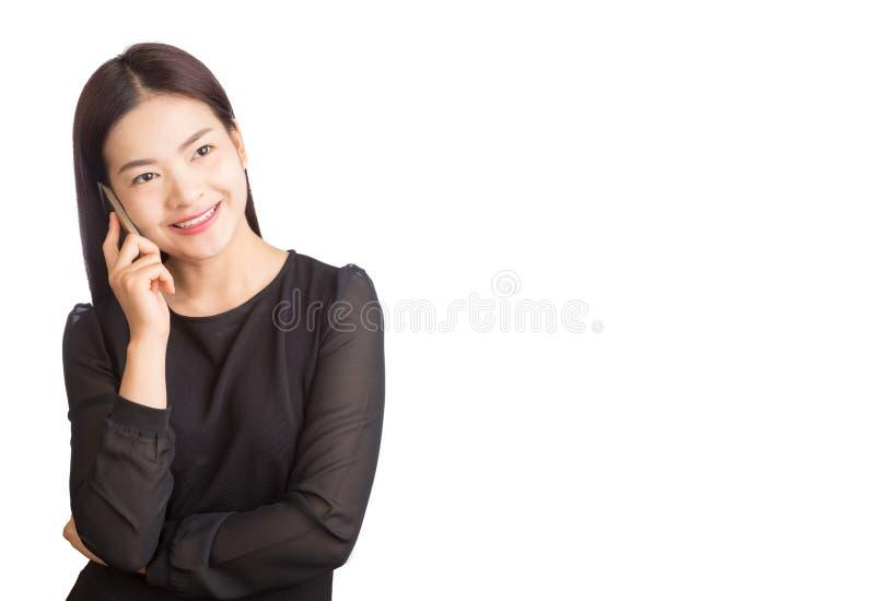 Asiatische junge glückliche lächelnde Frau, die auf ihrem Mobiltelefon, weiß spricht lizenzfreie stockbilder
