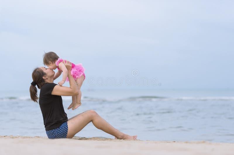 Asiatische junge Mutter, die oben ihr Baby auf sandigem Strand wirft lizenzfreie stockfotos