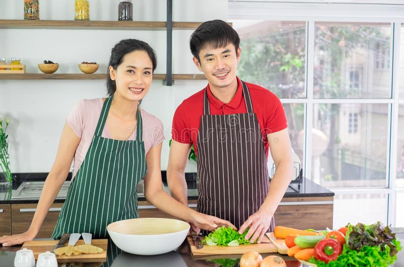 Asiatische junge Paare Stehen das Lächeln, das in der Küche kocht stockbilder