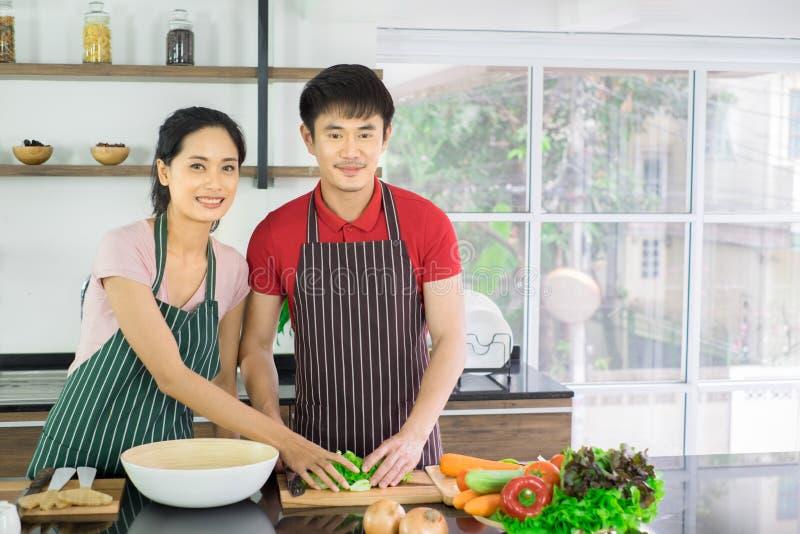 Asiatische junge Paare Stehen lächelndes in der Küche zu Hause kochen lizenzfreies stockfoto