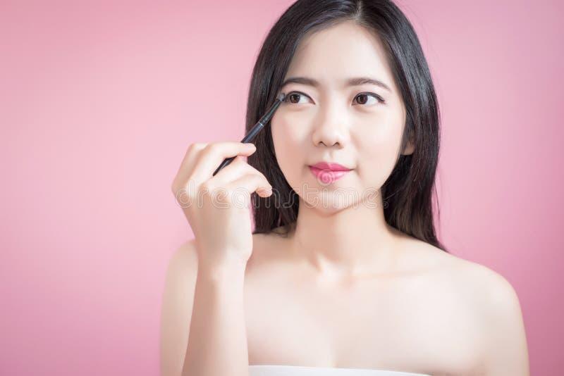 Asiatische junge Schönheit des langen Haares, die kosmetische Pulverbürste auf dem glatten Gesicht lokalisiert über rosa Hintergr stockfotografie