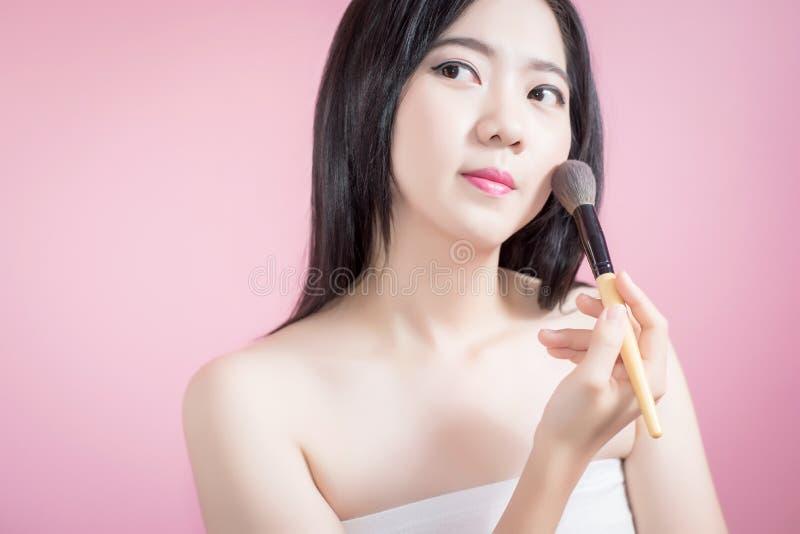 Asiatische junge Schönheit des langen Haares, die kosmetische Pulverbürste auf glattem Gesicht über rosa Hintergrund anwendet Nat lizenzfreie stockfotos