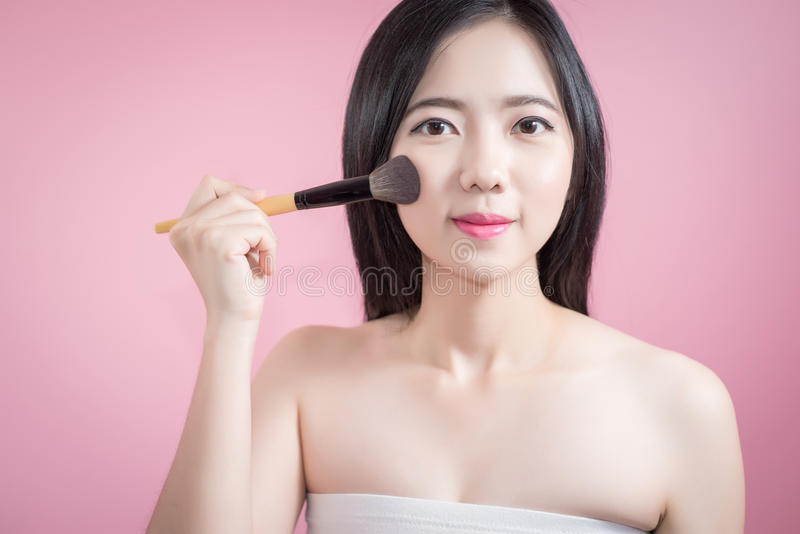 Asiatische junge Schönheit des langen Haares, die kosmetische Pulverbürste auf glattem Gesicht über rosa Hintergrund anwendet Nat lizenzfreie stockfotografie