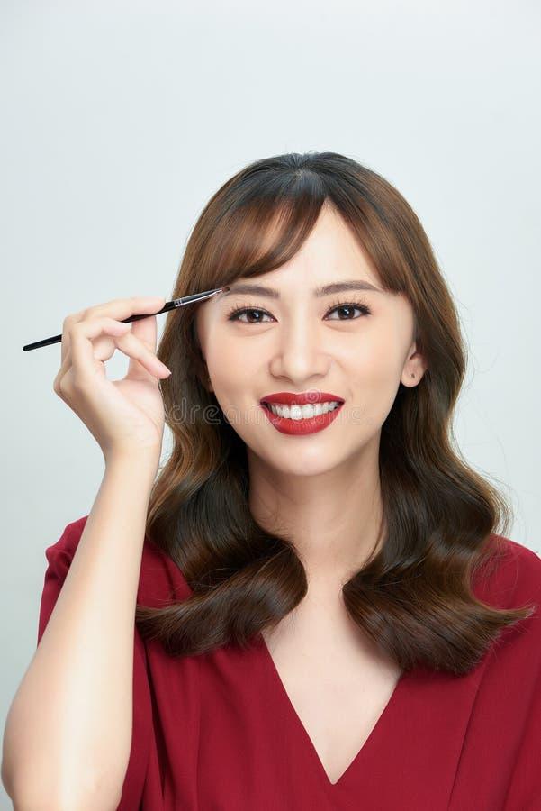 Asiatische junge Schönheit, die kosmetische Pulverbürste auf Augenbraue, natürliches Make-up, Schönheitsgesicht anwendet lizenzfreie stockbilder