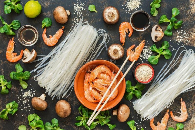 Asiatische Küche Bestandteile für das Kochen auf einem rustikalen Hintergrund Reisnudeln, Garnelen, Pilze Vid von oben lizenzfreie stockbilder