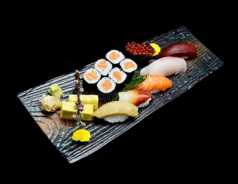 Asiatische Küche oder japanisches Lebensmittel Sushimedium eingestellt auf hölzerne Platte stockfotos
