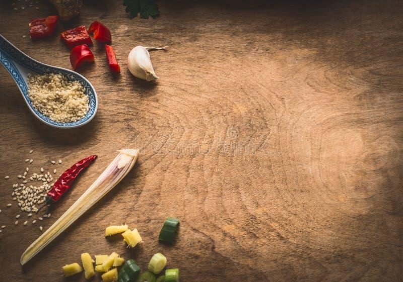 Asiatische Küche würzt Bestandteile gehackten Ingwer, Paprika, Samen des indischen Sesams, Knoblauch, auf rustikalem hölzernem Hi lizenzfreie stockfotografie