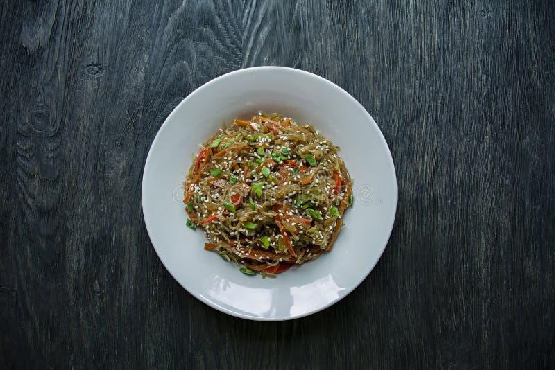 Asiatische K?che Salat von Zellophannudeln, gebraten mit dem Gem?se, verziert mit Gr?ns und Krabbenst?cken Funchoza korrekt lizenzfreie stockfotos