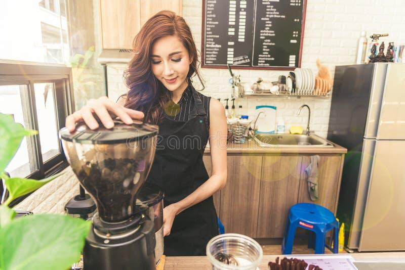 Asiatische Kaffeemaschinefrau, die Kaffee in der Kaffeestube macht Schönheit lizenzfreie stockfotos