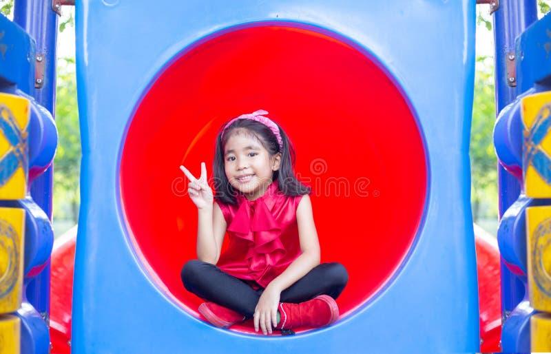 Asiatische Kinder des glücklichen Lächelns auf Kreis Plastik-tennel Spielparks lizenzfreie stockbilder