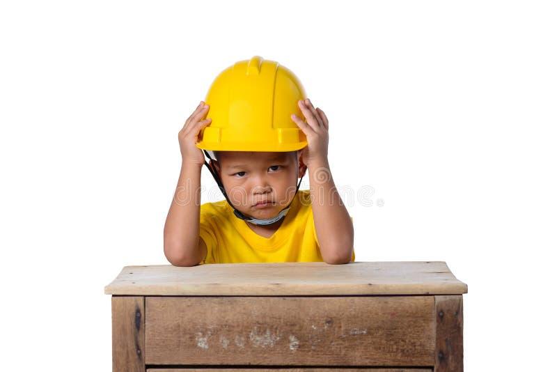 Asiatische Kinder, die den Schutzhelm und ernstes Gesicht lokalisiert auf wei?em Hintergrund tragen Kinder und Ausbildungskonzept stockbild