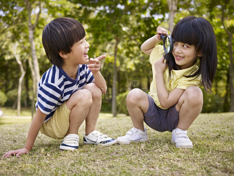 Asiatische Kinder, die draußen mit Vergrößerungsglas spielen lizenzfreies stockbild