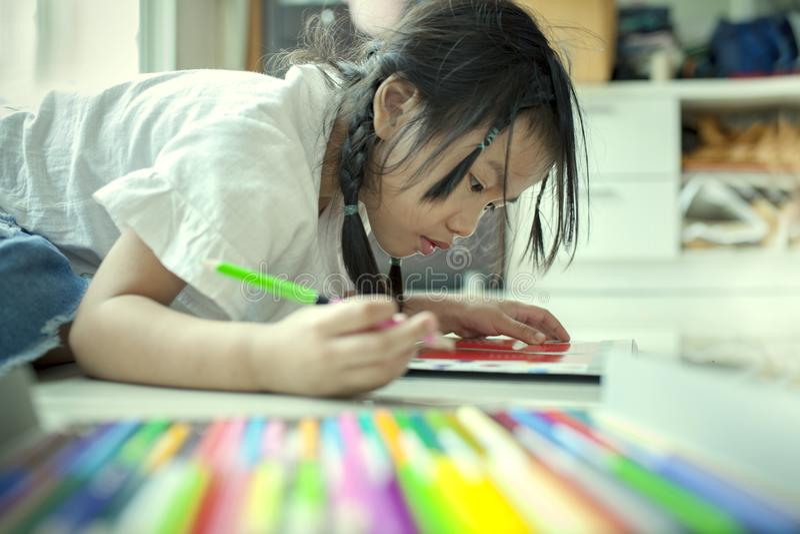Asiatische Kinder, die Farbbleistift auf Papierbuch I spielen und malen lizenzfreie stockfotografie